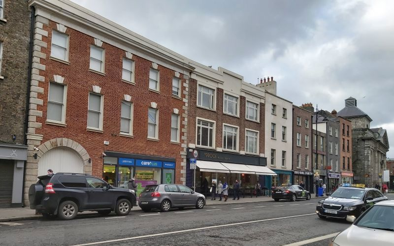 Thomas Street lined with buildings, focusing on one newly redone red brick one