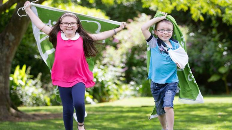 Young girl and boy each holding a green flag running in a park