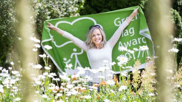 Woman holding a green flag for parks with wildflowers in the foreground